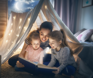 Photo of mother and 2 children reading under a bedspread tent